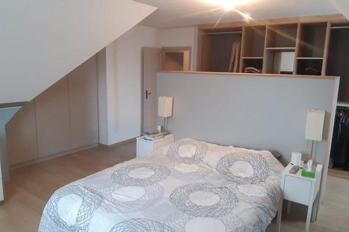 Aménagement d'une chambre avec un dressing , une tête de lit et un placard sous pente