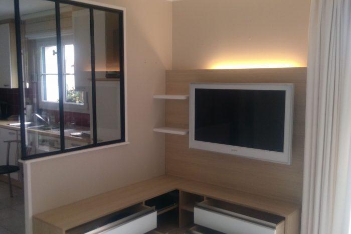 Sur cette photo, on voit le meuble tv ainsi que ses tiroirs qui sont ouverts. On voit également le jeu de lumière au dessus du meuble.
