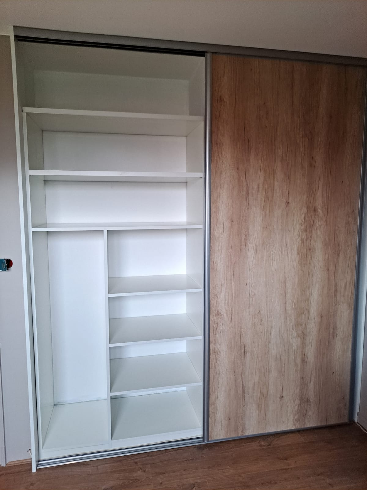 Sur cette photo, on peut voir le placard sur mesure avec une porte ouverte.
