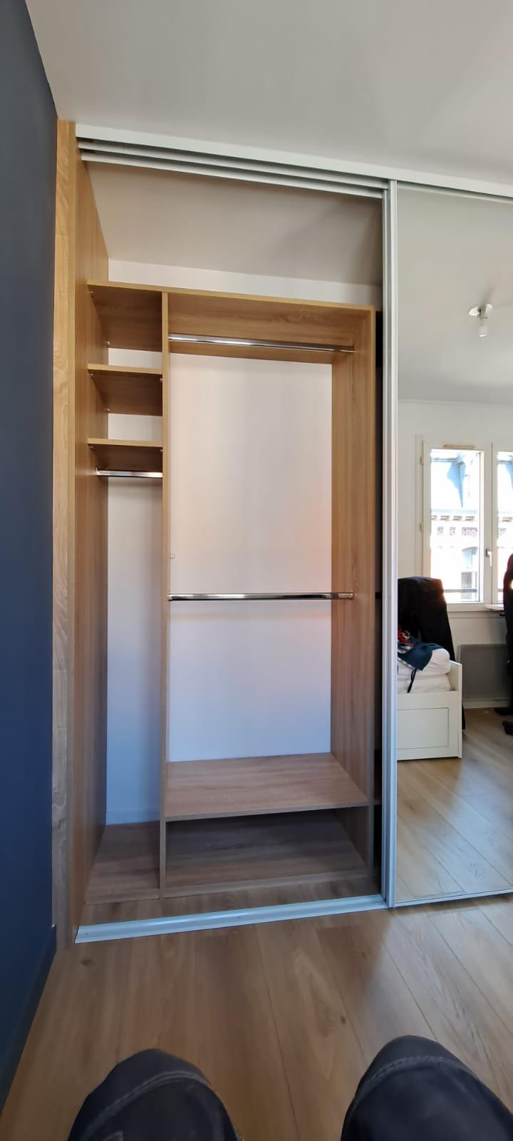 Sur cette photo, on voit également le dressing sur mesure avec les portes ouvertes et la porte miroir.