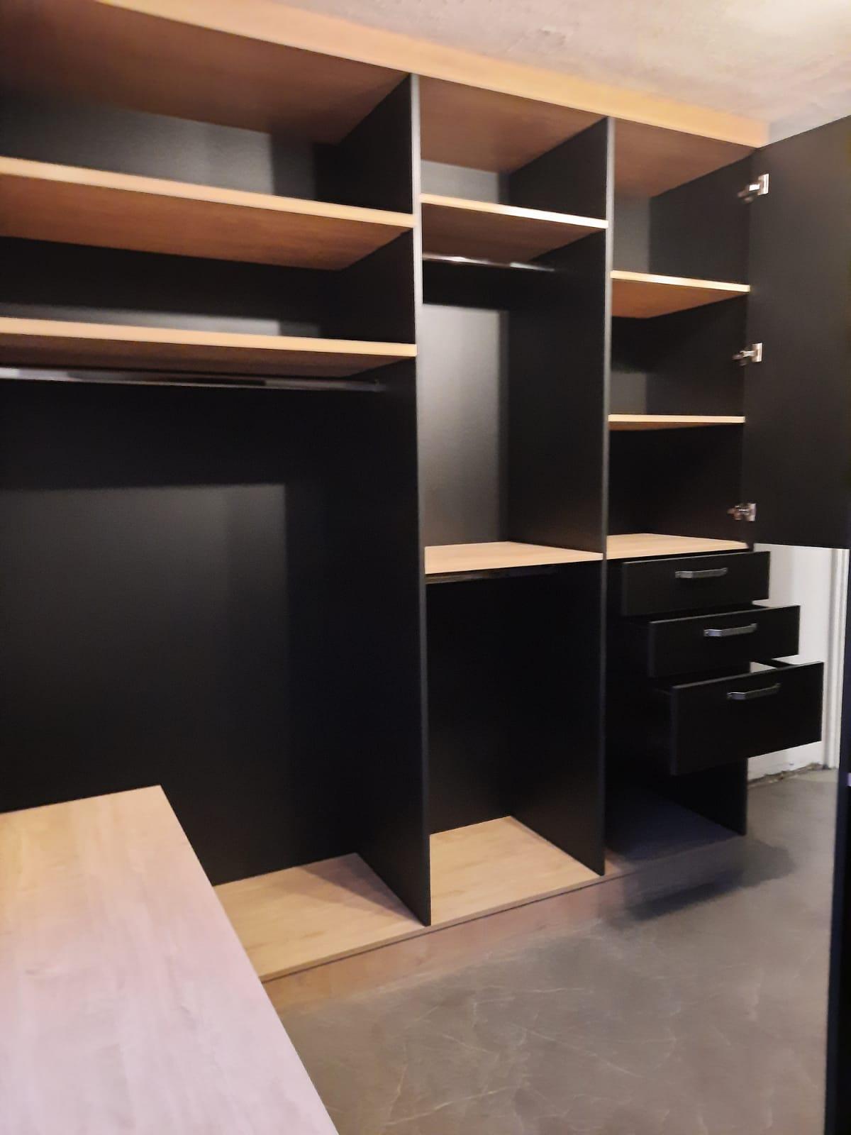 on voit un dressing de couleur noir avec les portes ouvertes.